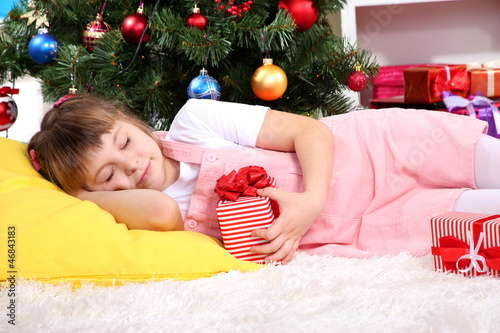 The little girl fell asleep with gift in their hands in