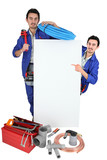 plumber with tools pointing at board
