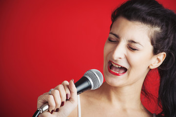 Beautiful girl singing with microphone against red background