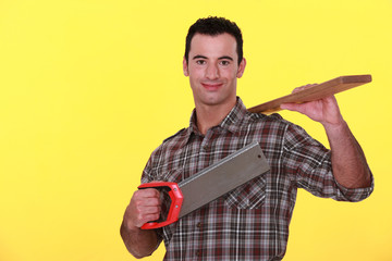 Builder holding a wooden plank