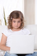 Little girl glued to laptop screen