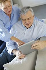 Modern senior couple websurfing on tablet