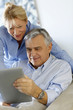 Modern senior couple websurfing on tablet