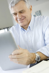 Senior businessman working on digital tablet from home