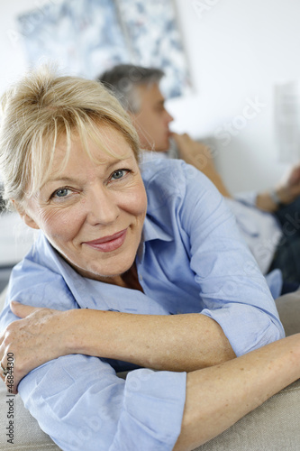 Senior woman sitting in couch, husband in background