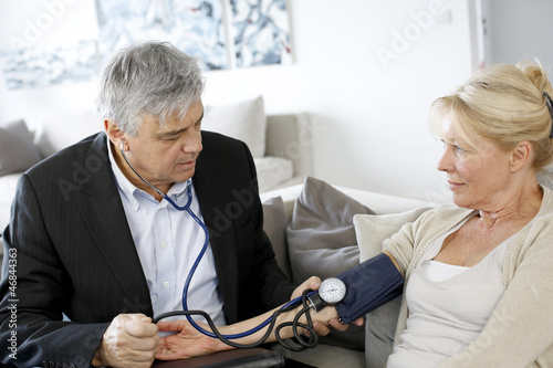 Doctor taking blood pressure to patient at home