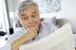 Senior man reading newspaper with puzzled look