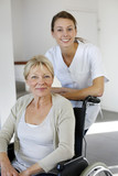 Nurse at home with elderly person in wheelchair