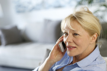 Senior woman at home talking on mobile phone