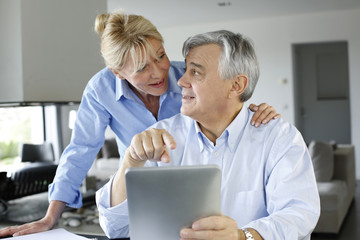 Senior couple looking at bank account on digital tablet
