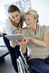Girl showing tablet to elderly woman in wheelchair