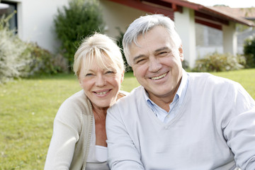 Smiling senior couple sitting in garden