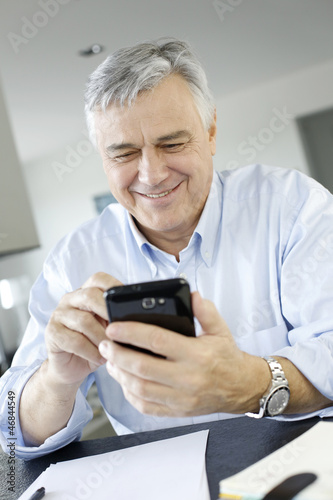 Portrait of senior businessman using smartphone
