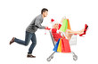 Happy guy pushing a female wearing christmas costume in a cart