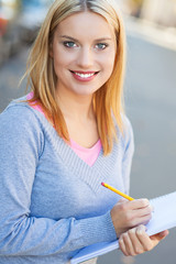 Young woman with notebook and pencil