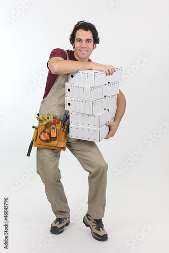 Man struggling to carry pile of boxes