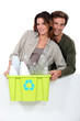 Smiling couple sorting garbage on white background