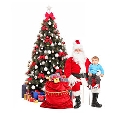 Santa Claus and child on his lap posing and a christmas tree