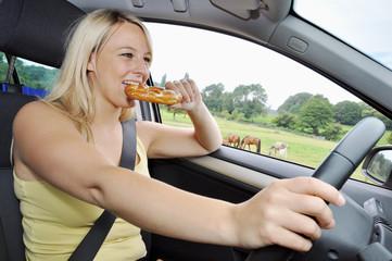 Junge Frau isst am Autosteuer