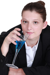 woman in a suit drinking a cocktail