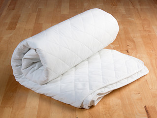 white mattress protection on wooden background