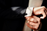 Close-up of a man in a tux fixing his cufflink. poster