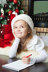 Funny girl in Santa hat writes letter to Santa