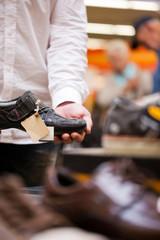 Mann kauft Schuhe im Supermarkt