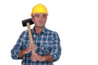 Man in plaid shirt holding heavy hammer