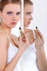Young woman applying lipstick in a mirror
