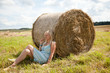 girl resting near straw bale