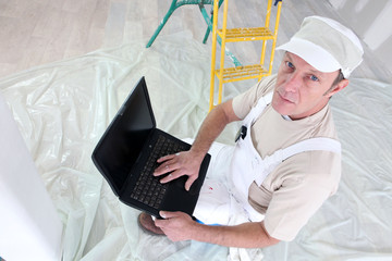 Painter holding laptop computer