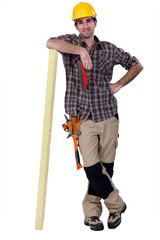 Carpenter leaning against a wooden plank