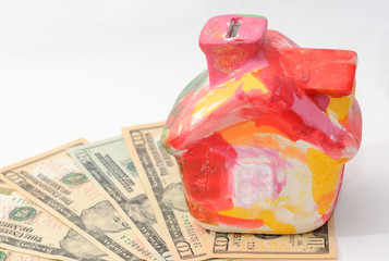 Colorful moneybox house stands on dollars