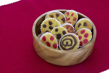 Small cakes on a wooden bowl over red towel