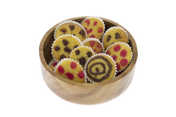 Small cakes on a wooden bowl isolated over white