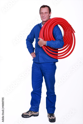 Tradesman holding coiled tubing around his shoulder