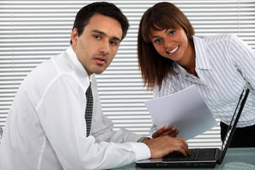 businessman and female colleague working on laptop