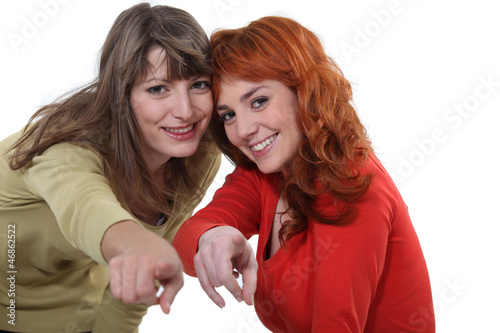 Two female friends pointing at the camera
