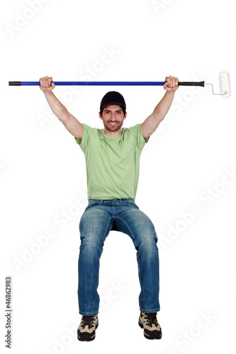 Tradesman sitting on an object and holding up roller