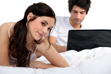Couple with a laptop on a bed