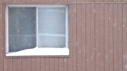 Window of apartment in a winter day. Slowly falling snow