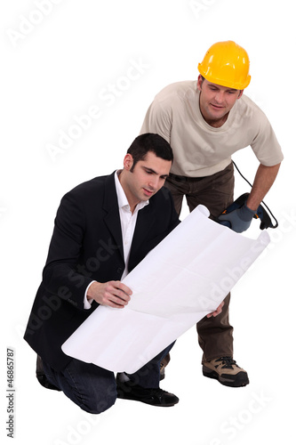 Construction worker consulting with an engineer over a drawing