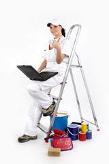 painter decorator with laptop leaning against ladder