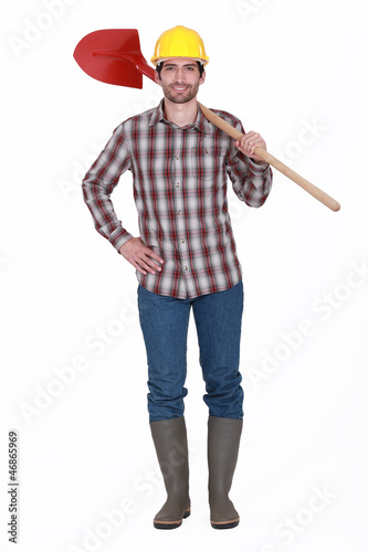 bricklayer standing against white background holding red shovel