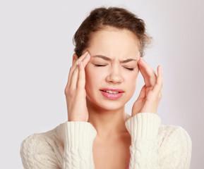 A woman with a headache holding head