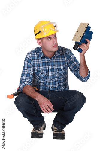 Worker with an electric sander