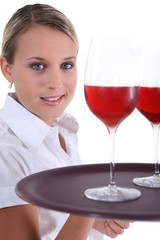 A waitress bringing two glasses of wine.