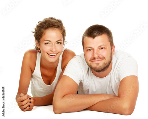 Happy couple lying on floor and smiling at camera