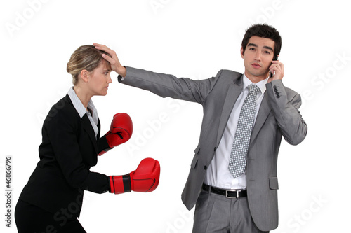 Woman with boxing gloves trying to hit woman